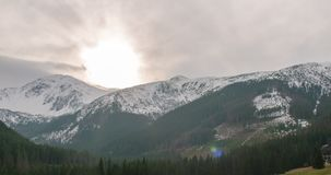 4K Time Lapse of Mountains Ridge with Snow, Sun and Clouds driven by Strong Wind. Awesome 4K Time Lapse of Mountains Ridge with Snow, Sun, Forest and Clouds stock footage
