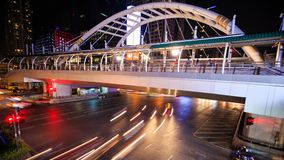 Time-lapse of public sky walk and traffic at Chong Nonsi sky train station at night, Bangkok, Thailand. 4k Time-lapse of public sky walk and traffic at Chong stock footage