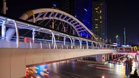 Time-lapse of public sky walk and traffic at Chong Nonsi sky train station at night, Bangkok, Thailand. 4k Time-lapse of public sky walk and traffic at Chong stock video