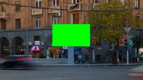 4K TIME LAPSE VIDEO. Advertising Billboard with green screen with long exposure cars in city, against backgrounds. Buildings with balconies, windows and signs stock video footage