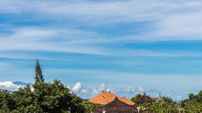 4K Time lapse of white fluffy full clouds in a blue sky with green tropical trees and traditional Balinese rooftops in. The background. Tropical island Bali stock footage