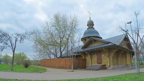 4K time-lapse. The wooden church in the old Russian style with a golden cross in the park of the city of Kiev. Cloudy weather in early spring stock video