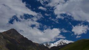 4K Timelaps-de Wolken zwemmen langzaam onder de groene bergen van de Kaukasus en ijs toneelpieken in de zomerzonsopgang Zonlichte stock videobeelden