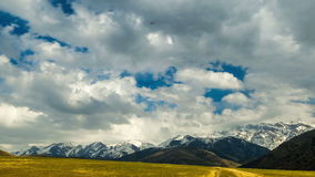 4K timelapse Επιπλέον σώμα σύννεφων πέρα από τον τομέα φθινοπώρου με μια άποψη των χιονοσκεπών βουνών απόθεμα βίντεο
