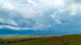 4K timelapse 冬天在春天领域,西天山的山麓小丘上覆盖 股票录像