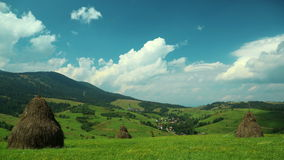 4K Timelapse of clouds and beautiful green fields with haystacks stock video