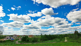 4k Timelapse clouds over the green field and small village. stock video