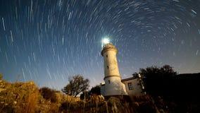 8K Timelapse da paisagem bonita da noite com o farol com giro do céu estrelado em um fundo filme
