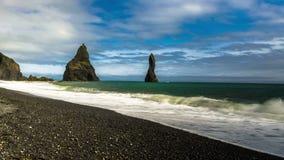 4K timelapse Golven die op het zwarte zandstrand breken Basaltkolommen, torenhoge 70 meters boven de wateren van het Noorden stock video