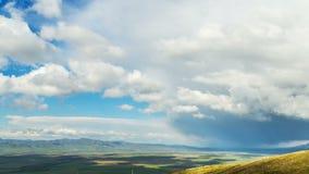 4K, timelapse Las nubes enormes se mueven rápidamente sobre los campos y los pueblos, la visión superior de la primavera en prima almacen de video