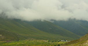 4k timelapse puffy clouds mass rolling over mountaintop & valley in tibet,village. stock footage