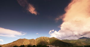4k timelapse puffy clouds mass rolling over Tibet mountaintop & valley,Sunset. stock footage