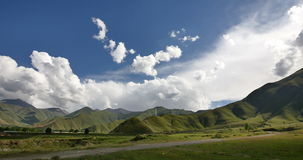4k timelapse puffy clouds mass rolling over Tibet mountaintop & valley. stock video footage