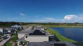 4k tiro aéreo de casas con los paneles de energía solar del eco en los tejados, pequeña visión suburbian con el lago almacen de metraje de vídeo