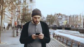4K toevallige geconcentreerde mens die smartphone gebruiken Knap gebaard creatief Europees mannetje in hoed het texting in de str stock videobeelden