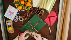 4K Top View from Above of Lady`s Hands Decorating Christmas Present with Ribbon. View at Lady`s Hands Decorating Christmas Present Box with Ribbon and Snowflake stock footage