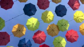 4K tracking shot of multicolored umbrellas suspended on wires. stock video
