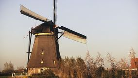 4K Traditional old Dutch rustic windmill working. Netherlands. European historical landmark. Farm mill spinning slowly. 4K Traditional old Dutch rustic windmill stock footage