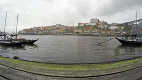 4K. Traditional Portuguese boats on Douro river, City of Porto, Portugal. Time Lapse in cloudy weather stock video footage