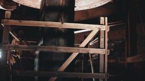 4K traditioneel molenmechanisme het werk close-up Reusachtige oude houten Nederlandse windmolenkern die binnen spinnen Oude Techn stock videobeelden
