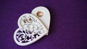 4k trouwringen in houten hartvakje in motie stock footage