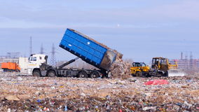 4K. Truck offloading waste into a huge landfill. 4K stock video footage