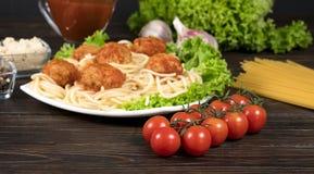 k?ttbollar i tagliatelle och basilika f?r tomats?s p? en tr?bakgrund arkivbilder