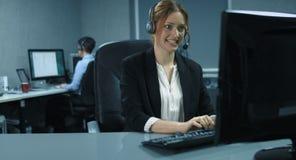 4K: Två kvinnliga callcentermedel arbetar på hennes dator med en hörlurar med mikrofon arkivfilmer
