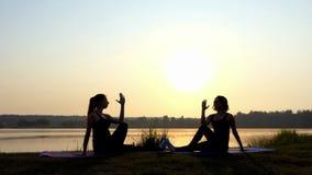 4k - Twee Vrouwen Sit Doing Yoga Eagle Exercise bij Zonsondergang op een Meerkust stock footage