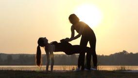 4k - Twee Vrouwen in Zwarte Sport Suits do Yoga, Één van hen is Zwanger stock video