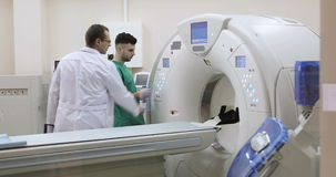 4K Two Doctors presses settings button of CT MRI scanner. stock video footage