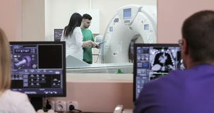 4K Two Doctors presses settings button of CT MRI scanner. Two doctors are sitting at the monitors with X-rays. New modern cancer treatment hospital stock video footage