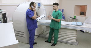 4K Two doctors are in a room with a CT scanner. The young specialist consults on mobile phone. Medical equipment: CT and MR scan, scanner, medical examination stock video