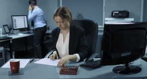 4K: Two female clerks work together in an office. The young woman controlled calmly some documents and drinks coffee. The older woman gets excited about steady stock footage