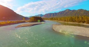 4k UHD aerial view. Low flight over fresh cold mountain river at sunny summer morning. Green trees and sun rays on stock footage