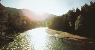 4k UHD aerial view. Low flight over fresh cold mountain river at sunny summer morning. Green trees and sun rays stock footage