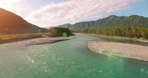 4k UHD aerial view. Low flight over fresh cold mountain river at sunny summer morning. Green trees and sun rays on. 4k UHD aerial view. Low flight over fresh stock video