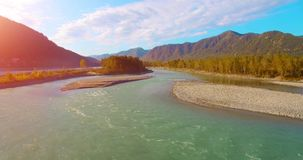4k UHD aerial view. Low flight over fresh cold mountain river at sunny summer morning. Green trees and sun rays on. 4k UHD aerial view. Low flight over fresh stock footage