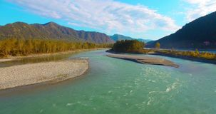 4k UHD aerial view. Low flight over fresh cold mountain river at sunny summer morning. Green trees and sun rays on. 4k UHD aerial view. Low flight over fresh stock video footage