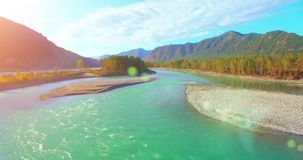 4k UHD aerial view. Low flight over fresh cold mountain river at sunny summer morning. Green trees and sun rays on stock video footage