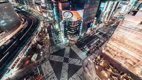 4K UHD Aerial view time-lapse of Ginza road intersection at night, crowded people walking on zebra crossing and car traffic light stock video footage