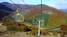 4K UHD footage of ski lift or elevator going down. With empty seats over colorful autumn mountain landscape background stock video