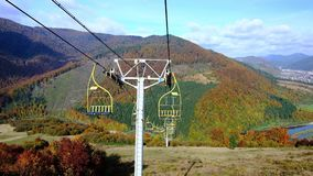 4K UHD footage of ski lift or elevator going down. With empty seats over colorful autumn mountain landscape background stock footage