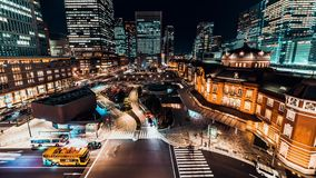 4K UHD time-lapse of car traffic at Tokyo Station at night with Japanese people crossing roads. Tokyo tourist attraction concept stock video footage