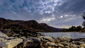 Time lapse shot of a river near mountain forest. Huge rocks and fast clouds movenings. Horizontal slider movement. 4k UHD timelapse shot of the splashing water stock footage