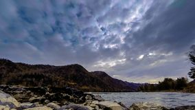 Time lapse shot of a river near mountain forest. Huge rocks and fast clouds movenings. Horizontal slider movement. 4k UHD timelapse shot of the splashing water stock video footage
