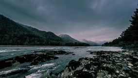 Time lapse shot of a river near mountain forest. Huge rocks and fast clouds movenings. 4k UHD timelapse shot of the splashing water in a river near mountain stock footage