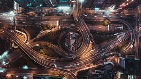 4K UHD top view time-lapse of car traffic at night on multiple lane highway, winding road, and roundabout in Hong Kong city stock video footage