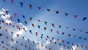 4K ultrarapid av triangulära ganska flaggor för färgrik designgarnering som blåser på vinden som hänger på bakgrund för blå himme lager videofilmer