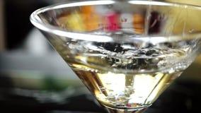 4k ultrarapidskott av olivgrönt plaska in i martini lager videofilmer